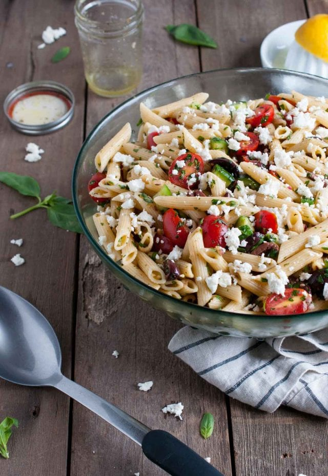 Greek pasta salad with juicy tomatoes, crunchy cucumbers, fresh herbs, olives and other goodies, all tossed in a tangy lemon vinaigrette.