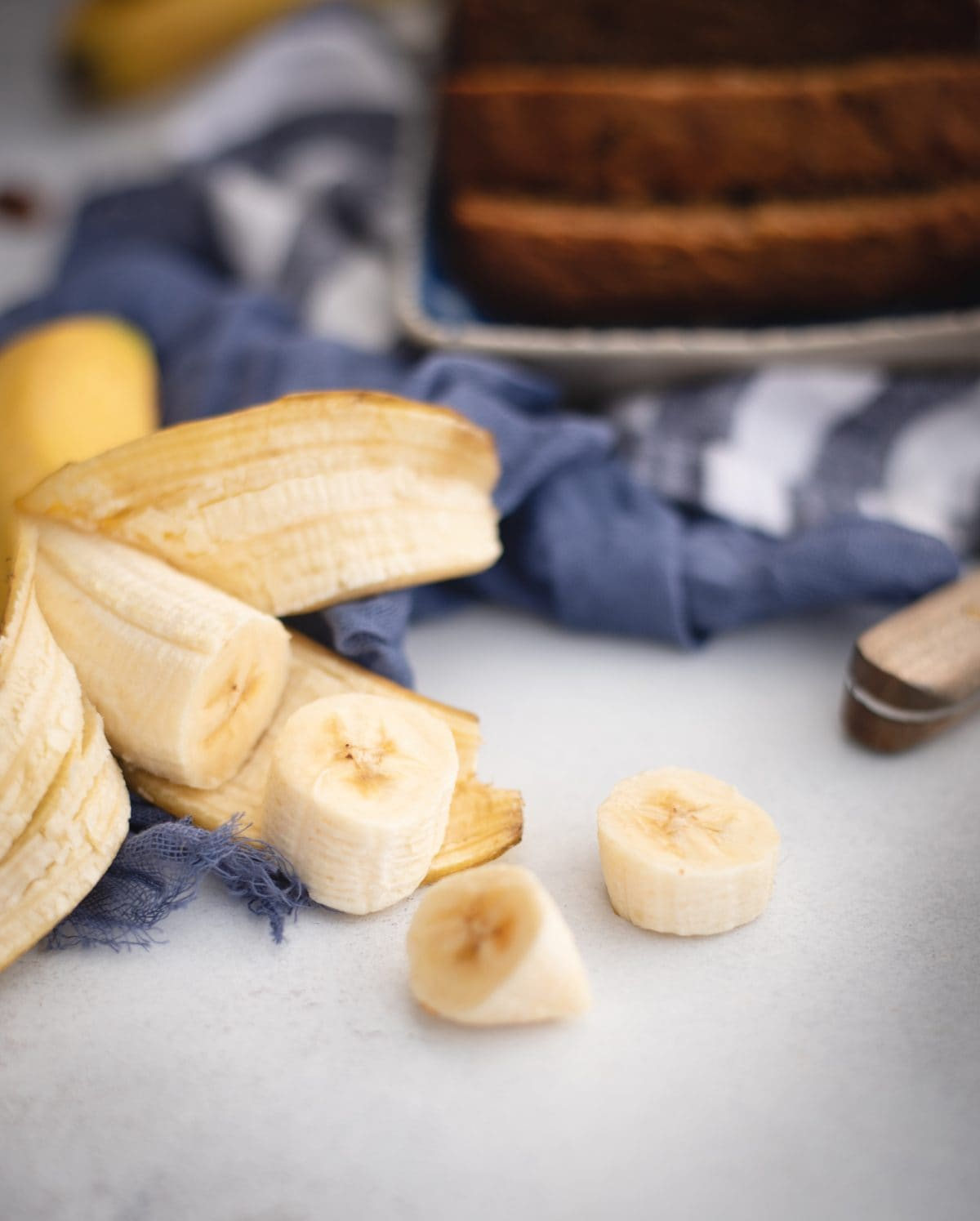 Sliced banana with banana bread loaf in background