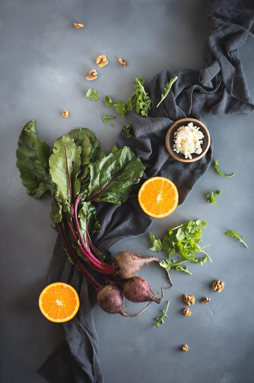 Overhead picture of arugula salad with roasted beets and orange slices ingredients