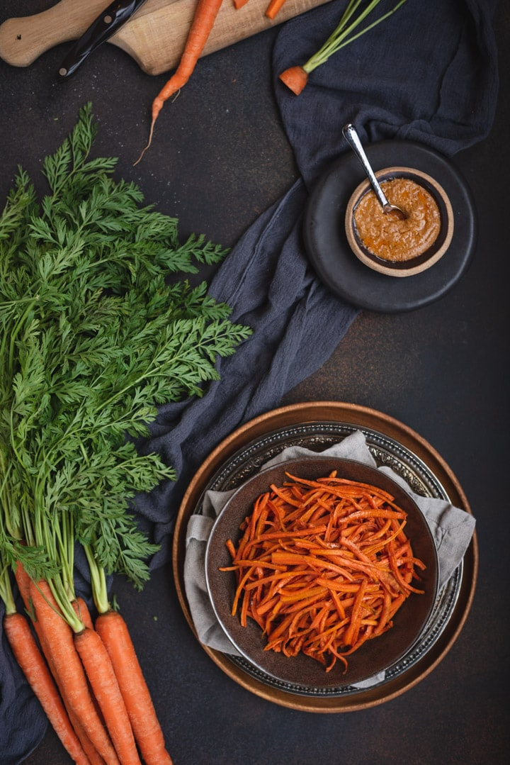 overhead close up of bowl of carrot fries on dark background with peanut sauce