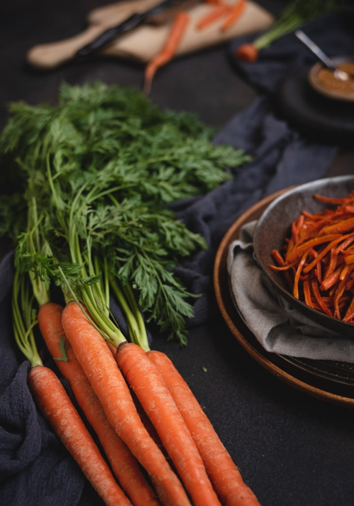 close up picture of dark bowl of carrot fries with raw carrots next to them