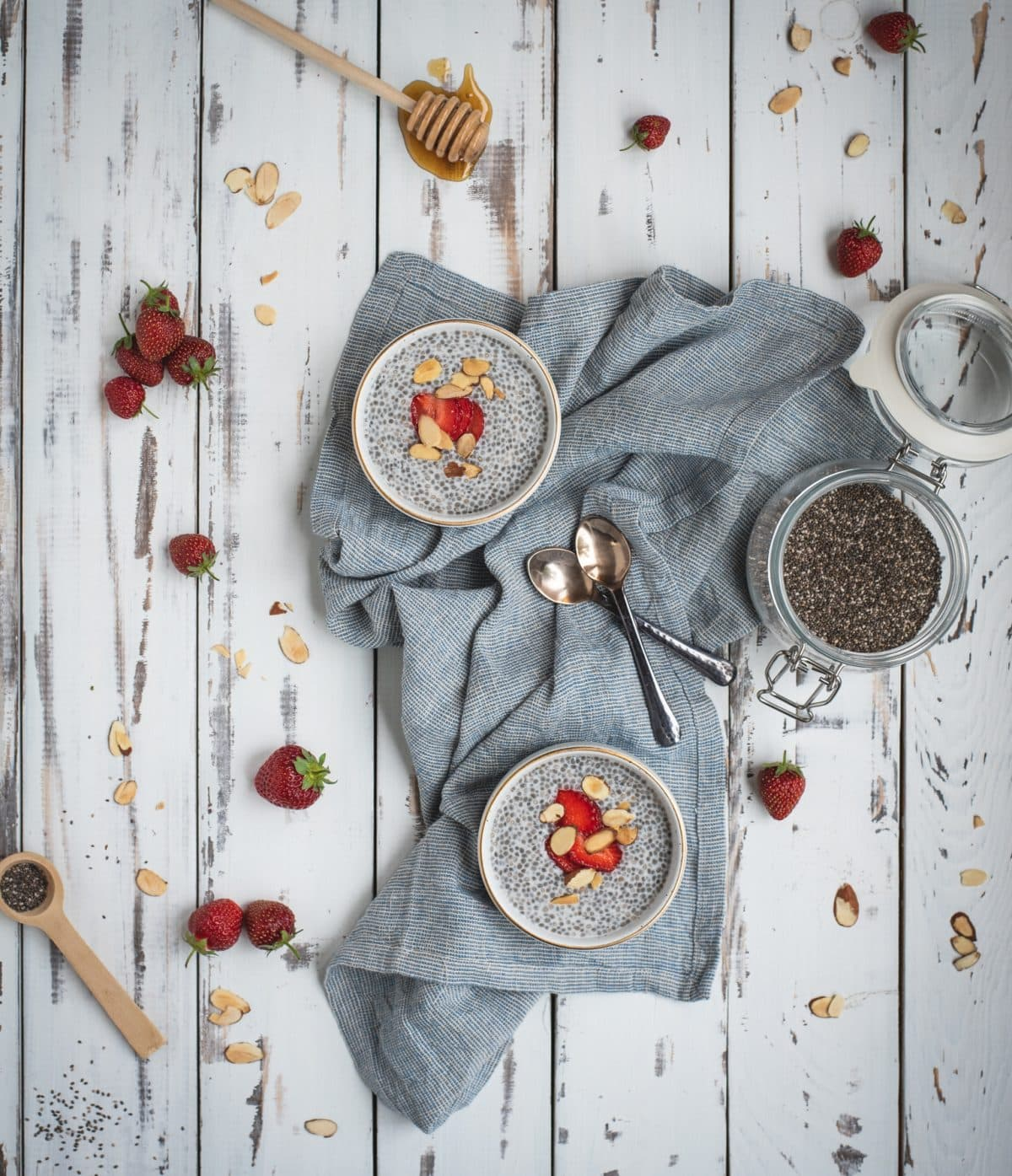 Overhead picture of almond chia seed pudding in two bowls with strawberries and honey