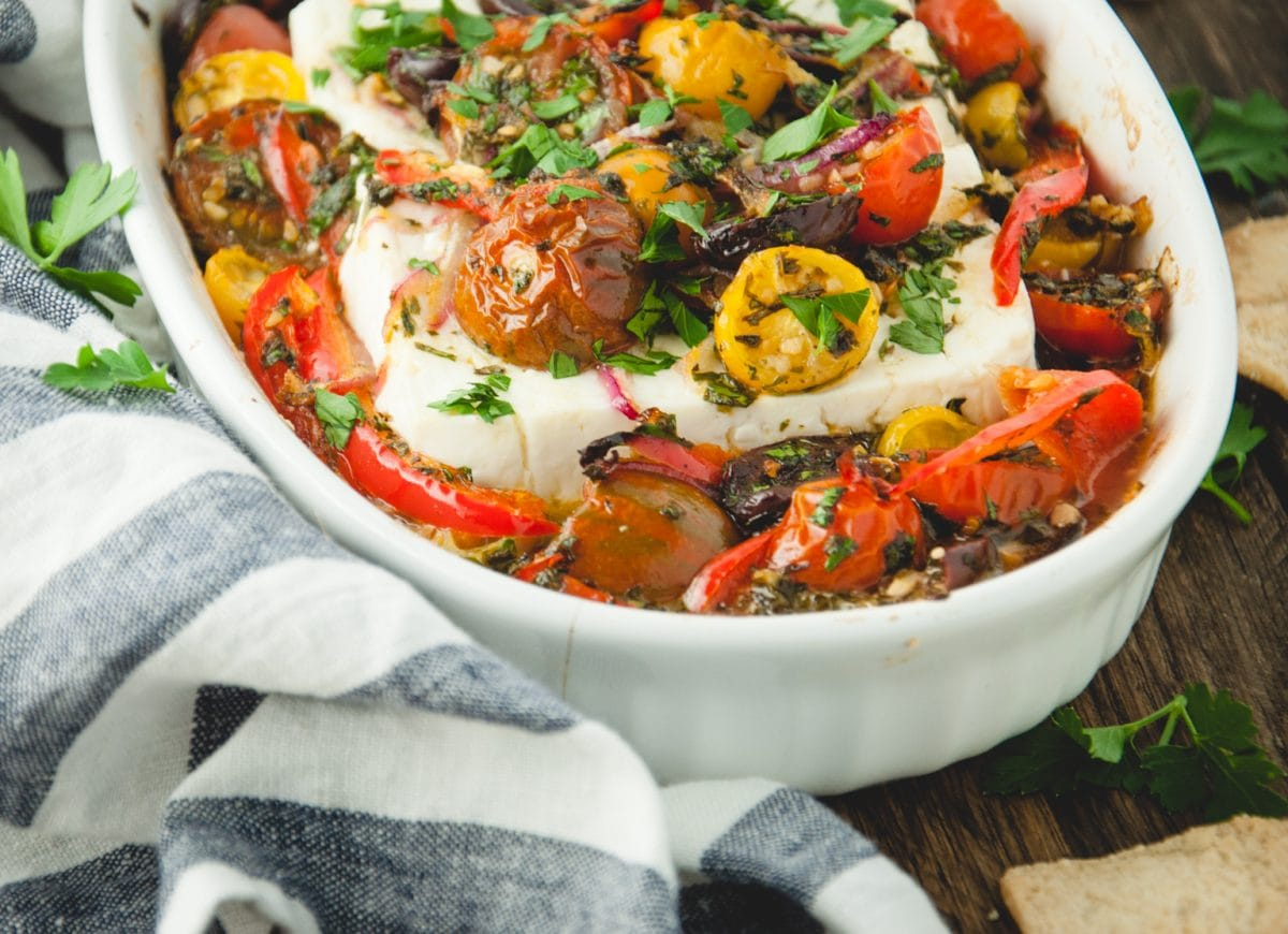 Baked feta with roasted vegetables in a white dish