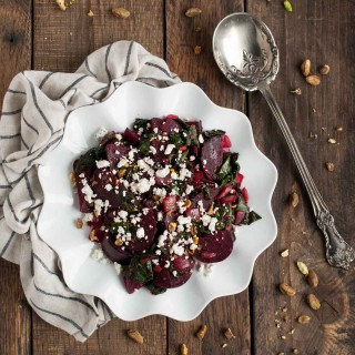 These light, delicious sautéed beet greens are tossed in tangy vinegar and spices before being topped with roasted beets, crushed pistachios, and crumbles of feta cheese.