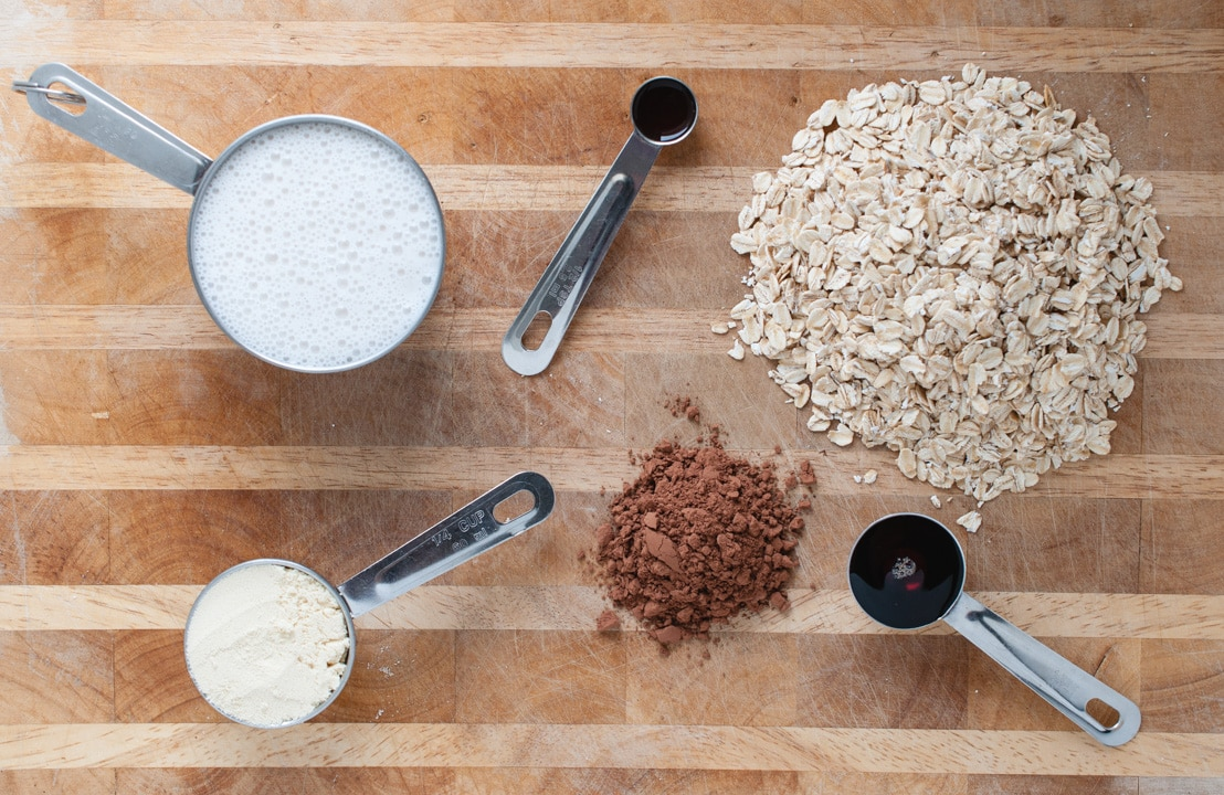 cutting board with oats, milk, and other overnight oat ingredients