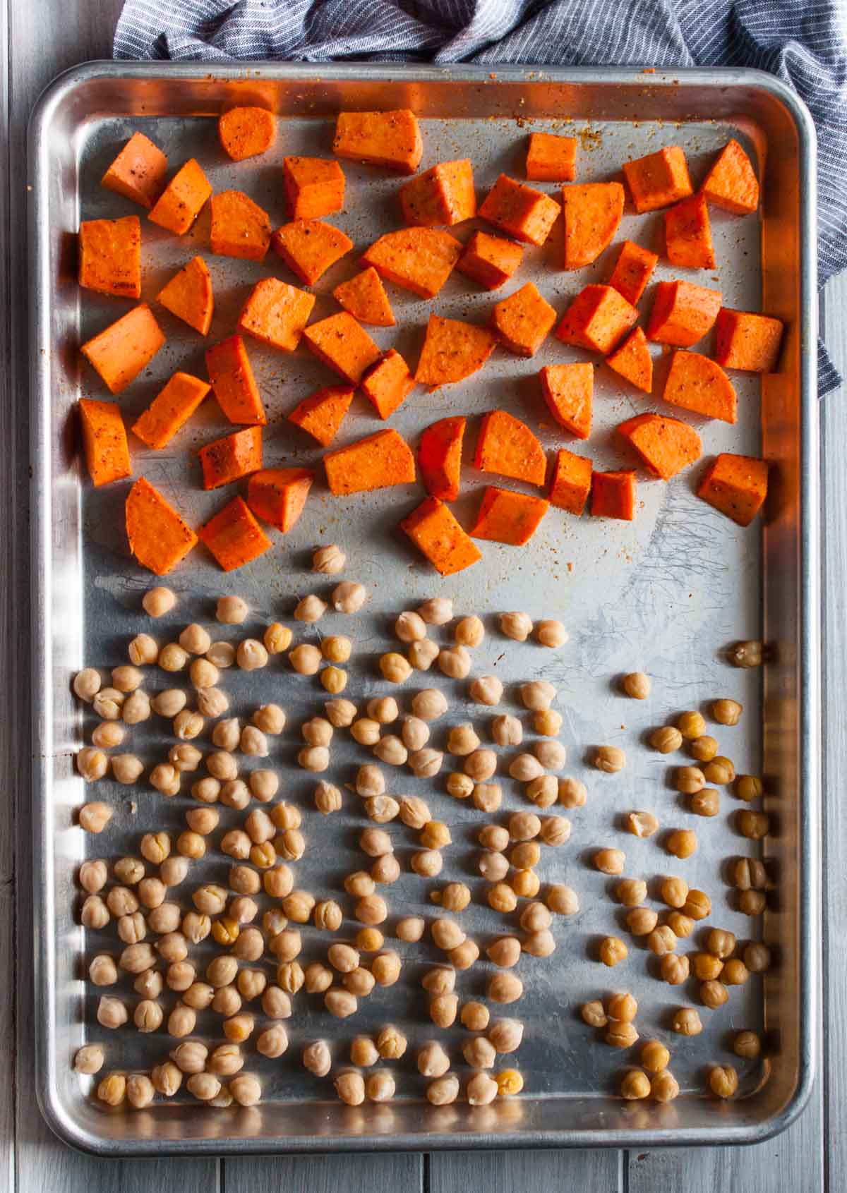 Tasty arugula sweet potato salad with zesty yet creamy tahini dressing, crunchy roasted chickpeas, and a pop of tartness from juicy pomegranate arils.