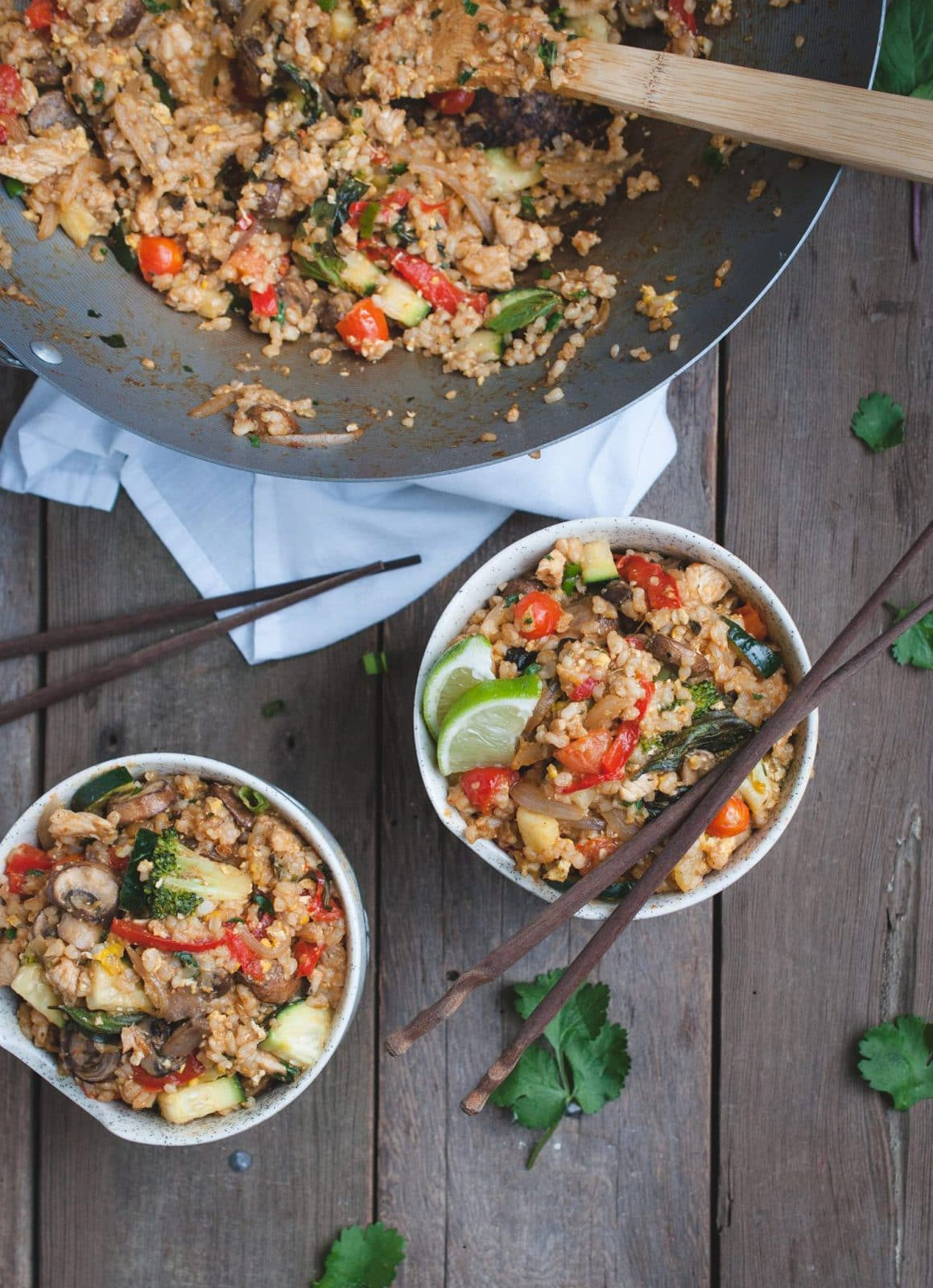 Close up overhead shot of two bowls of Thai fried brown rice