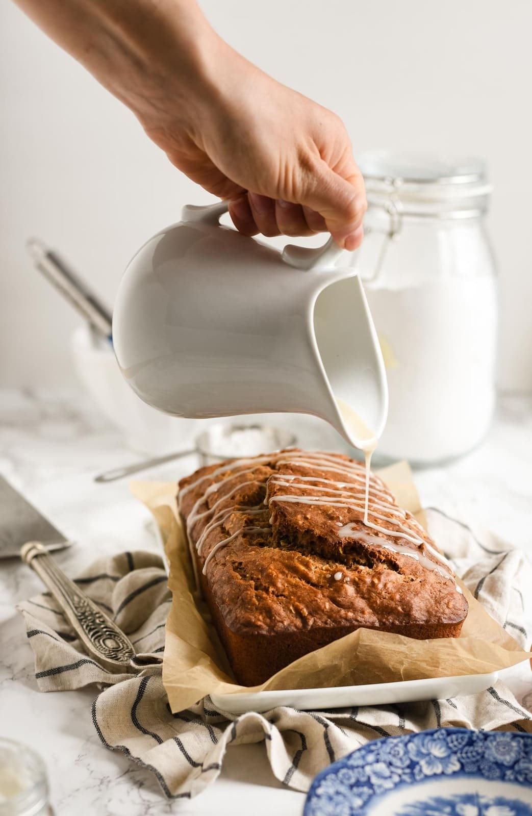banana bread with glaze being poured on top