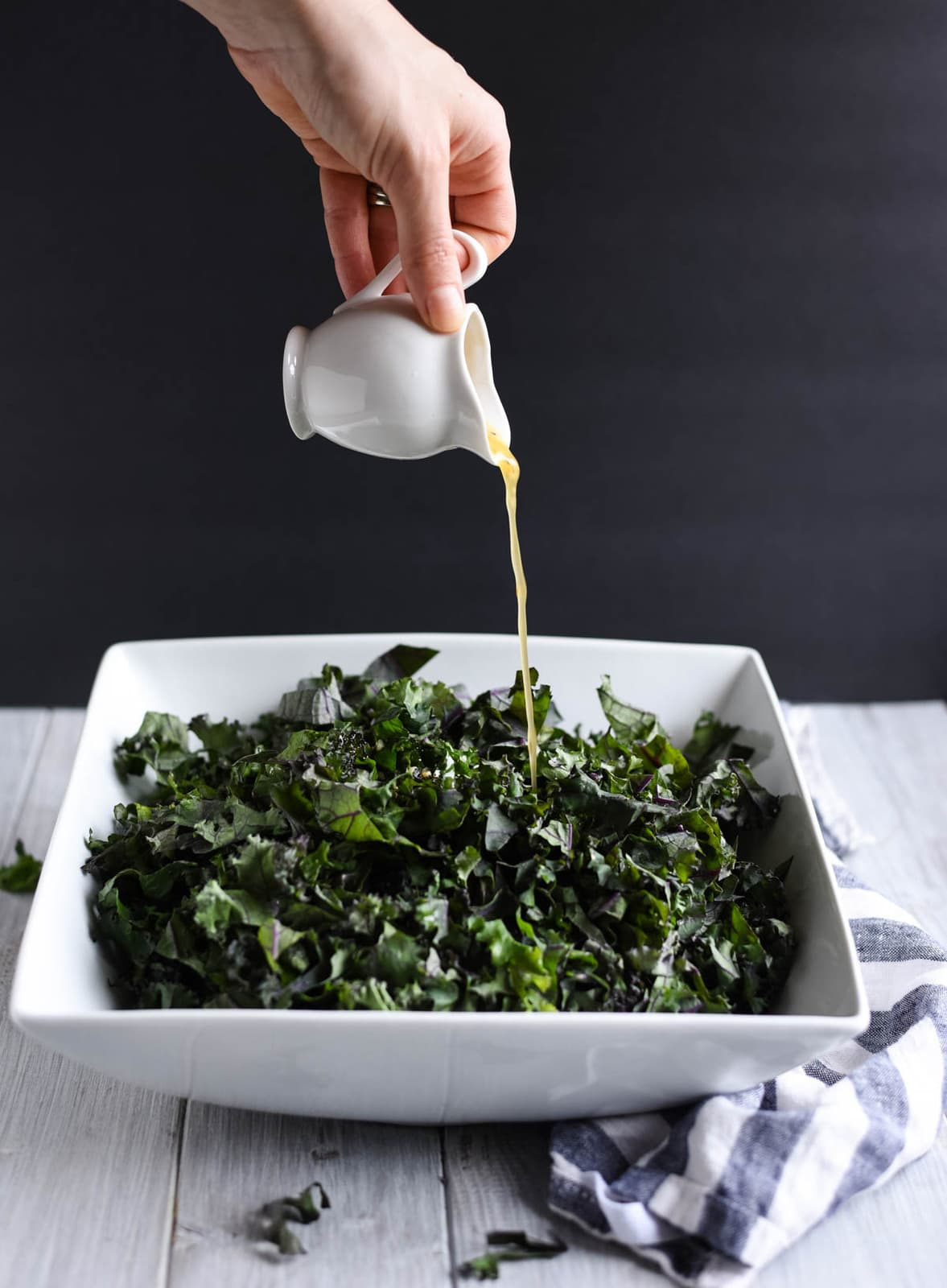 Dressing being drizzled onto kale salad