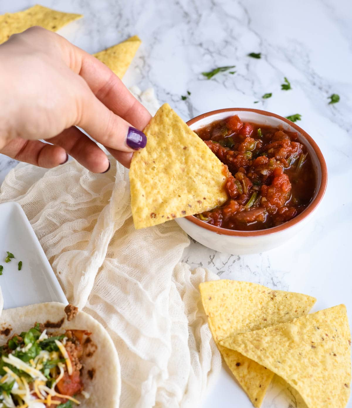hand dipping chip into salsa