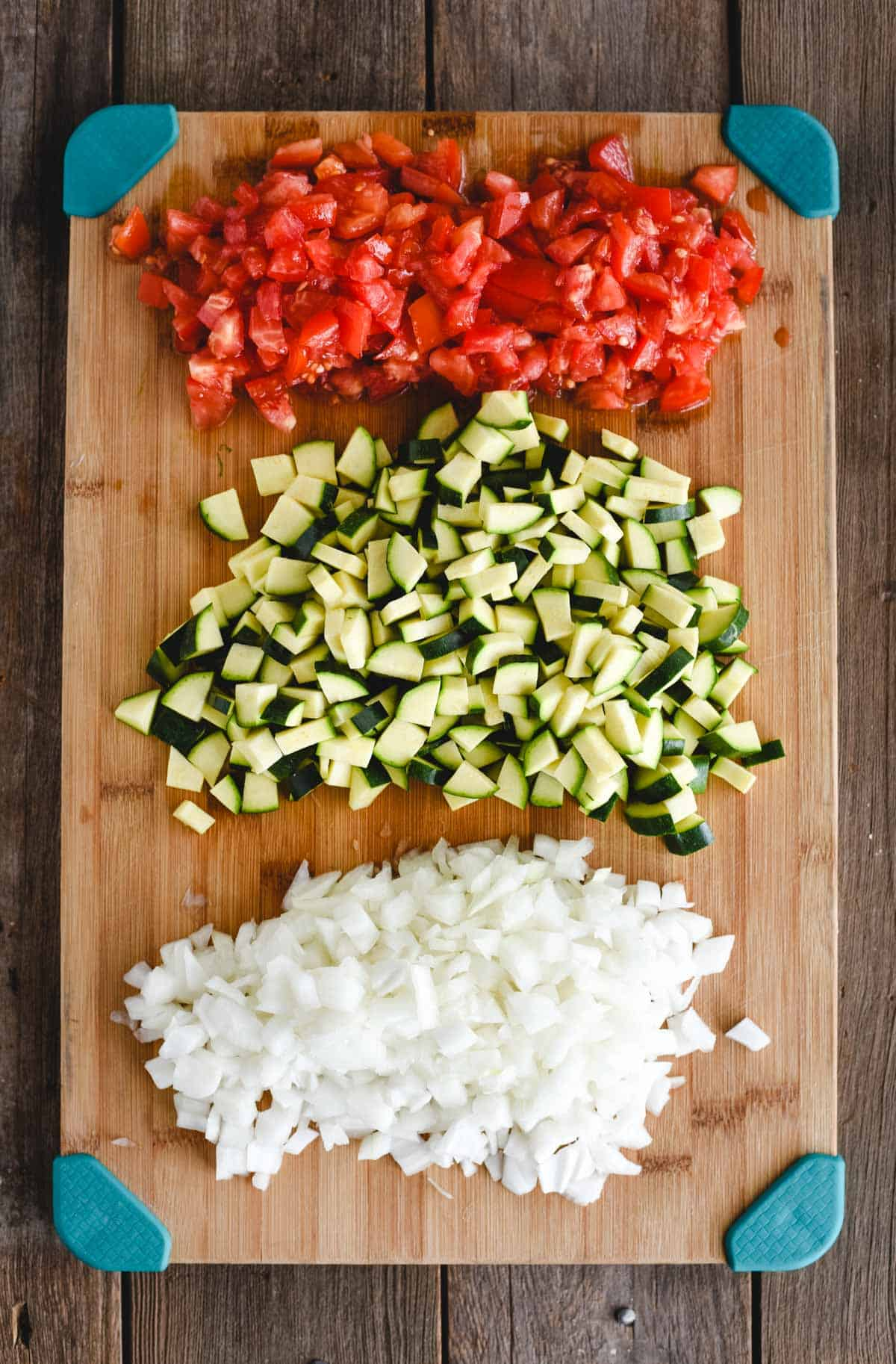 cutting board with zucchini, tomato, and onion chopped on it