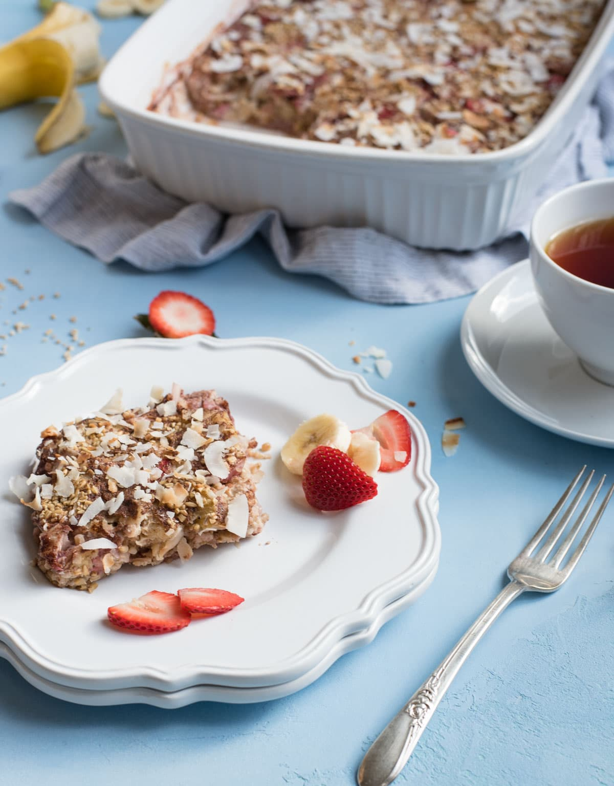 Strawberry Banana Steel Cut Oat Bake slice on a plate with full dish in background
