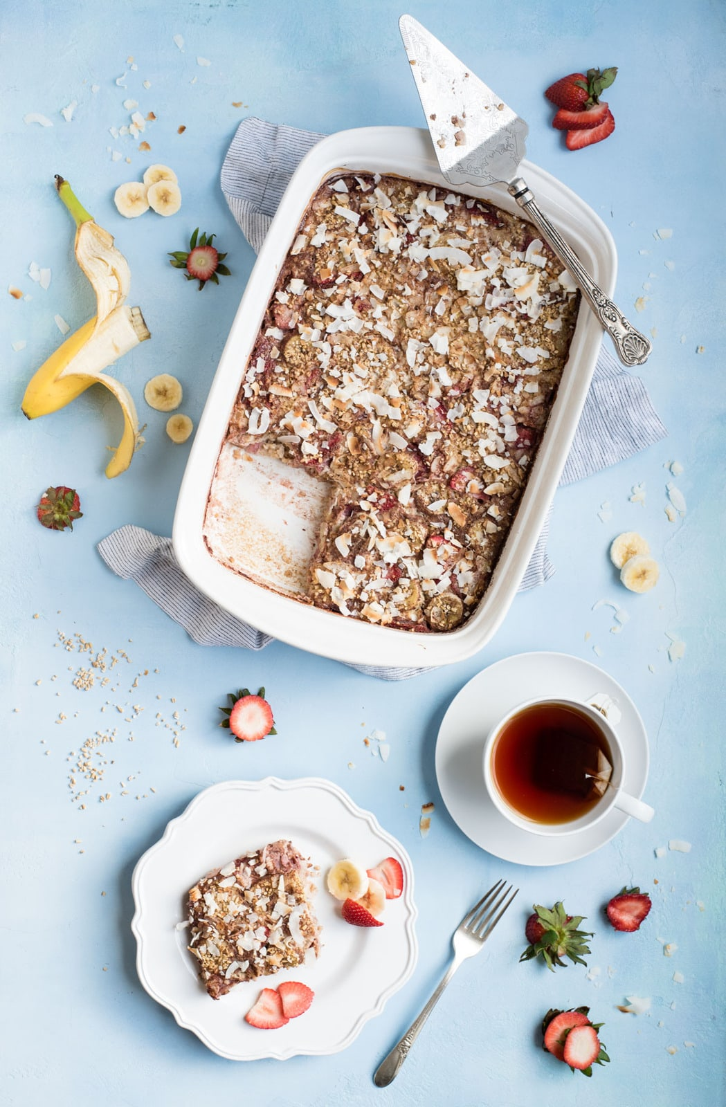 Strawberry Banana Steel Cut Oat Bake overhead picture of dish with one serving and cup of tea