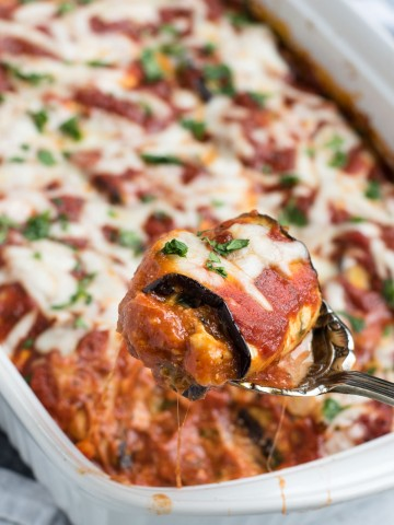 eggplant lasagna roll ups with one roll being served from a spoon