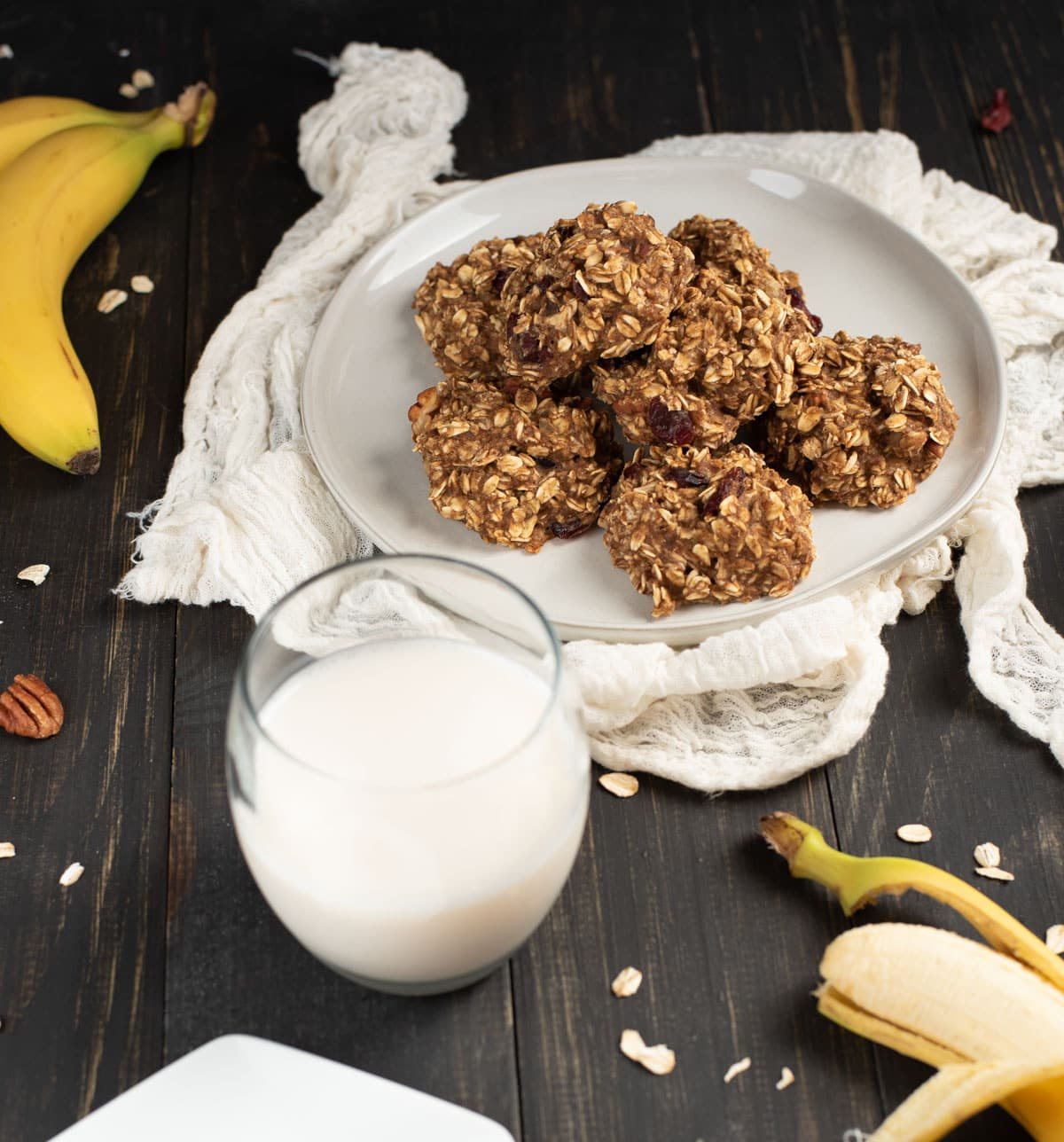 stack of healthy banana oat cookies on a plate with milk