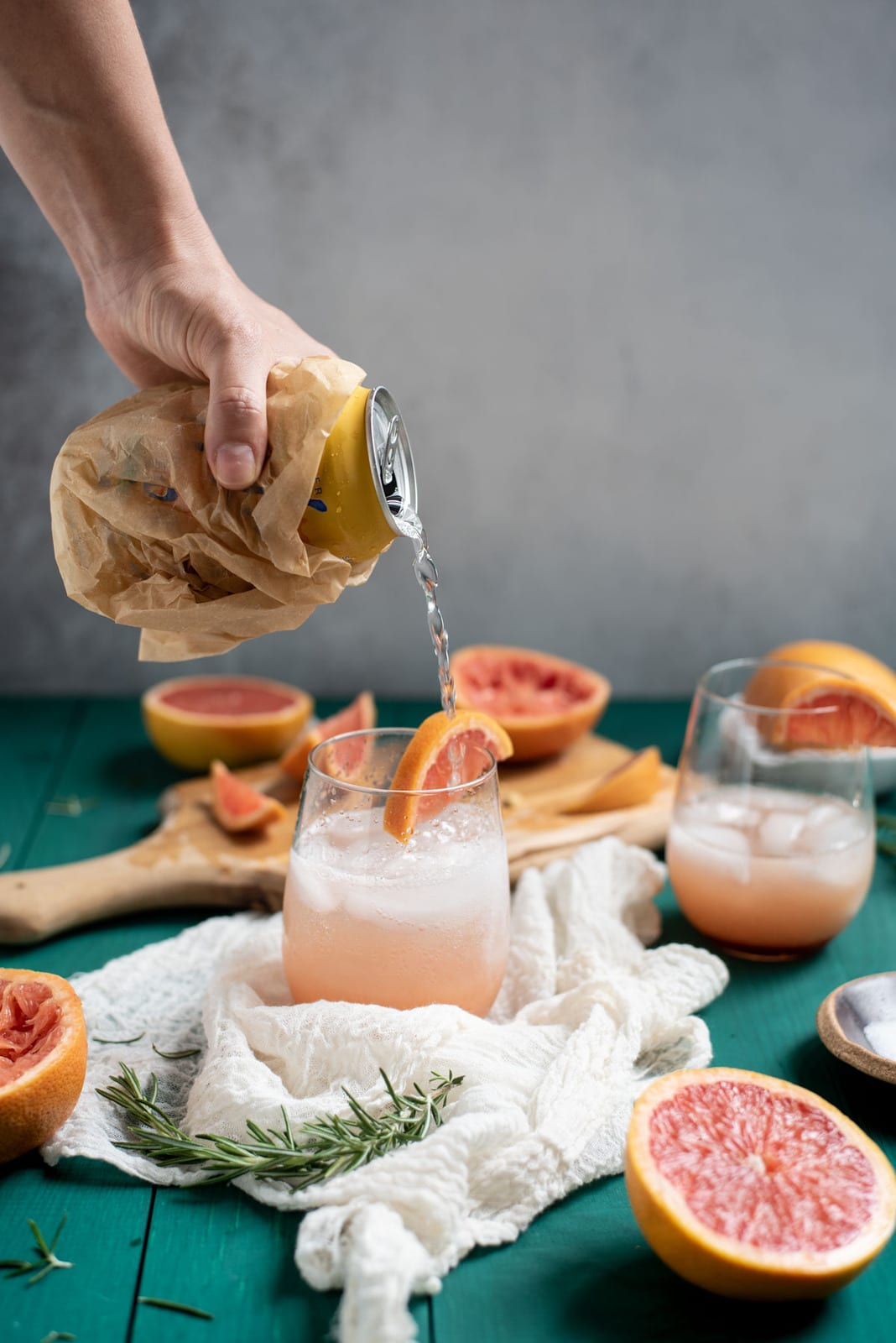 Pouring seltzer water into Rosemary grapefruit mocktail