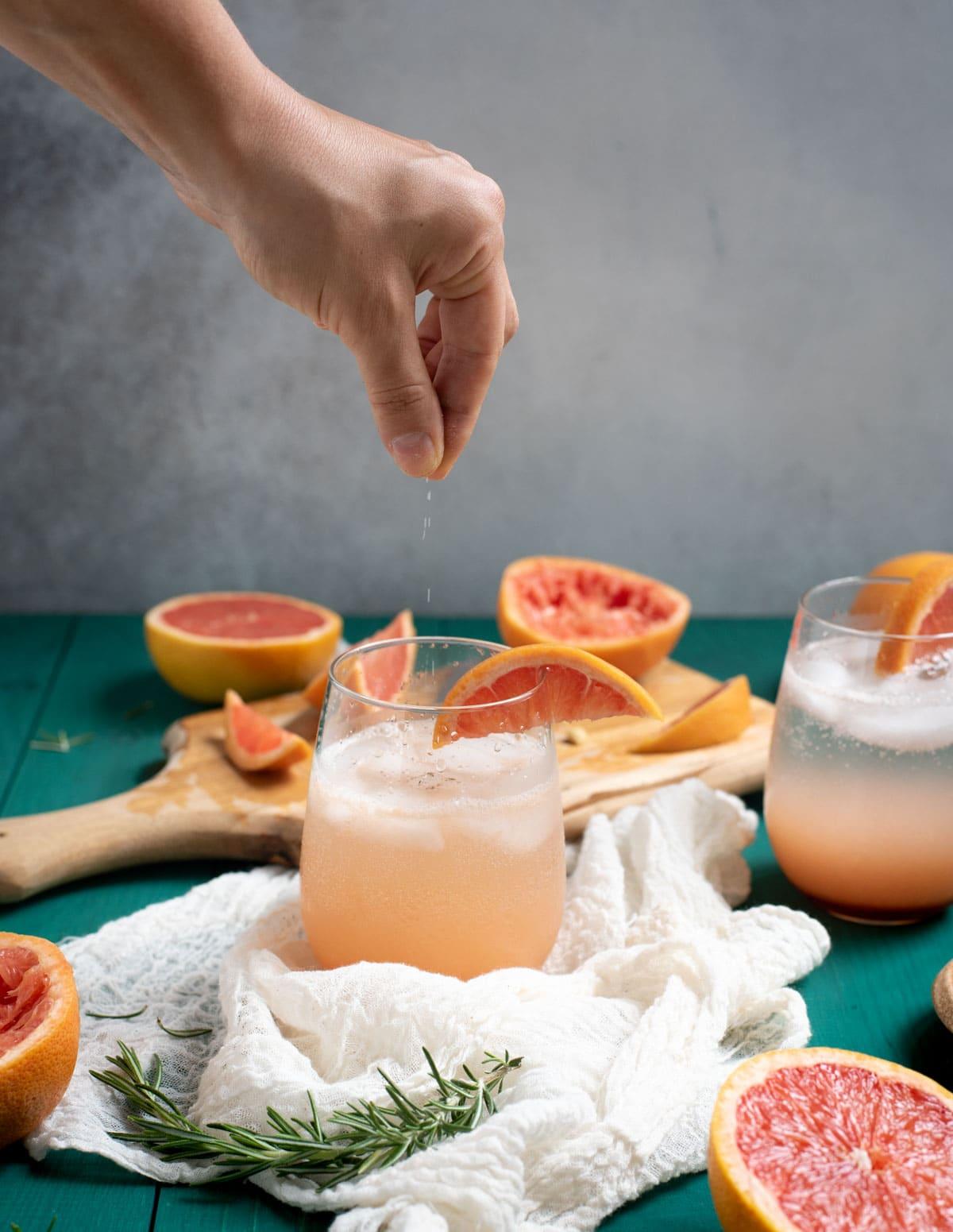 Hand sprinkling salt in Rosemary grapefruit mocktail