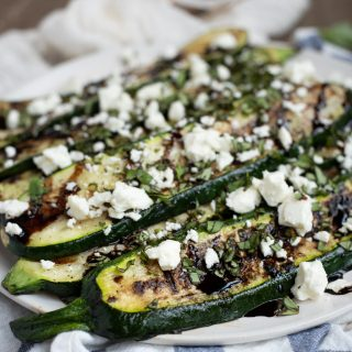 Picture of grilled zucchini on a plate with feta, basil and balsamic glaze
