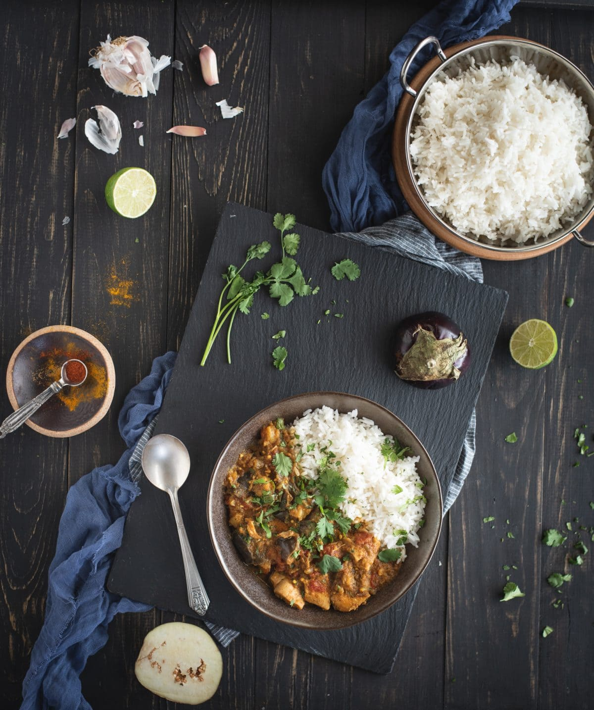 Overhead picture of Instant Pot chicken curry with eggplant with ingredients on dark background