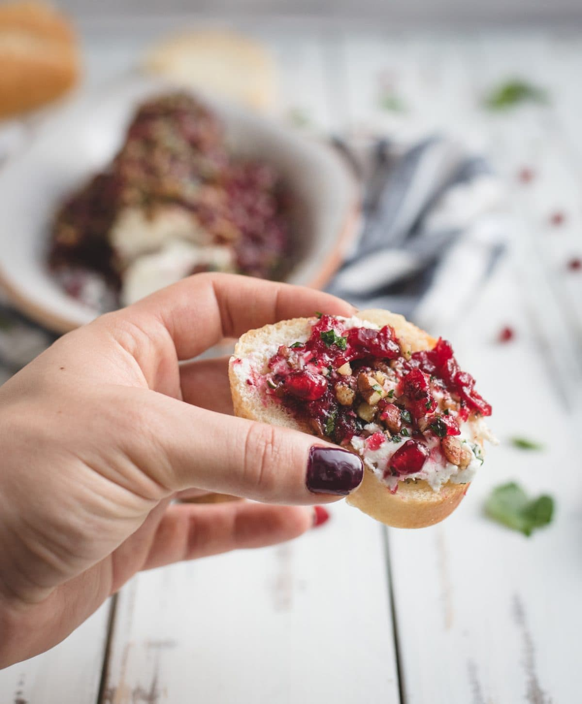 picture of hand holding cranberry herb goat cheese log on bread