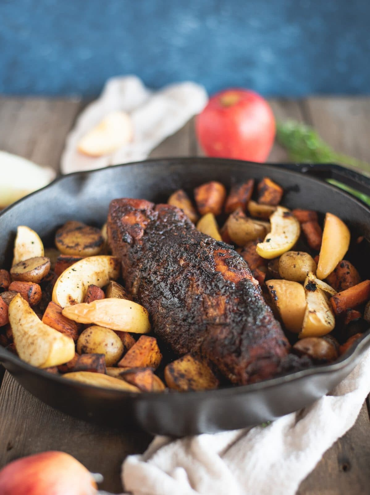 Pork Tenderloin with Apples and Root Vegetables in a skillet with blue background