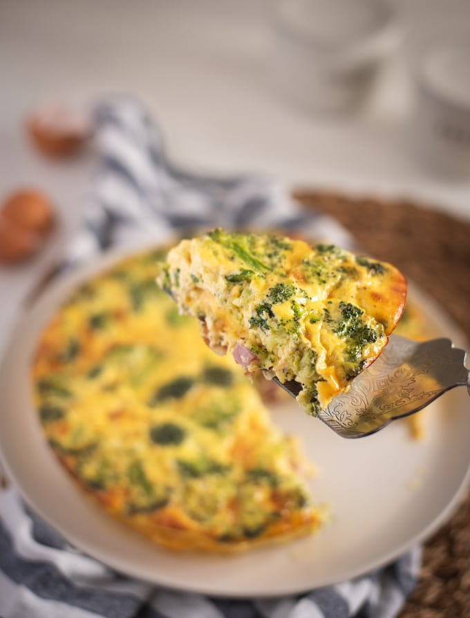 slice of ham and broccoli quiche held up on serving utensil