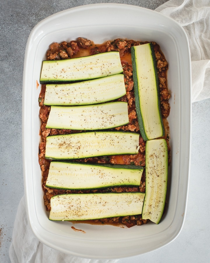 baking dish with red sauce and zucchini slices