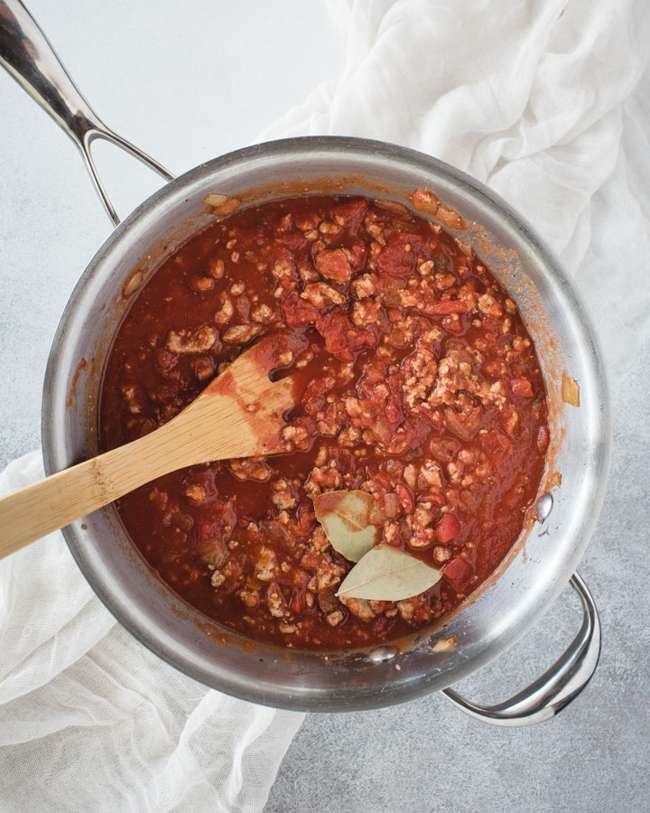 pan with red sauce and bay leaf
