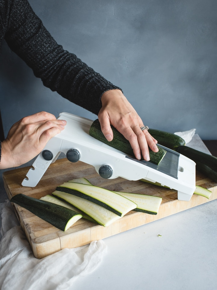 zucchini being sliced on mandolin slicer