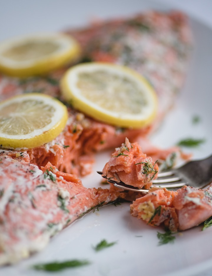 Bite of oven baked salmon with lemon and dill on a fork