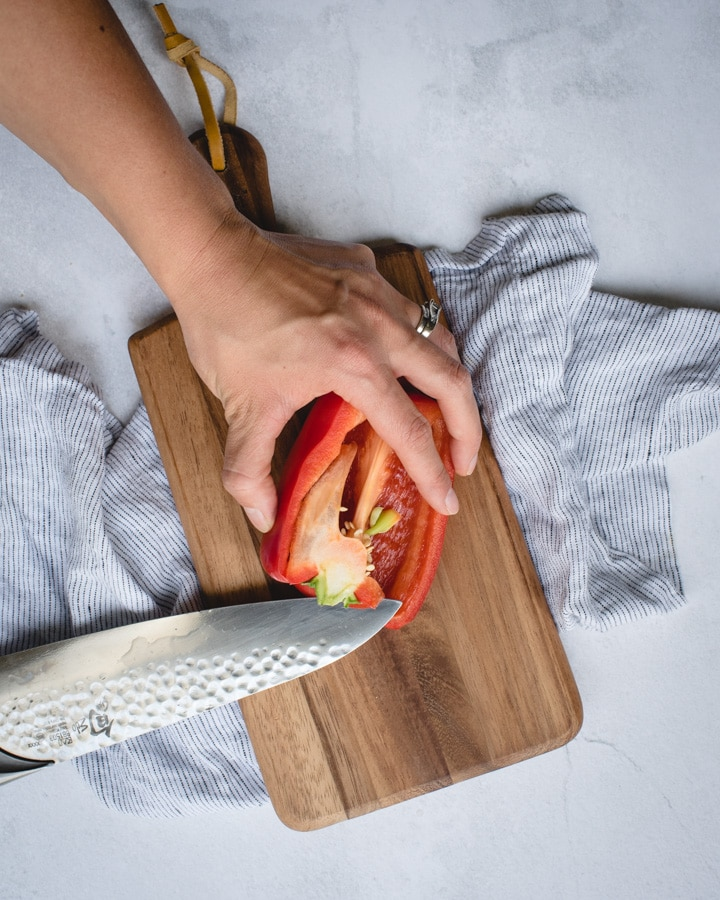 hand coring bell pepper on cutting board