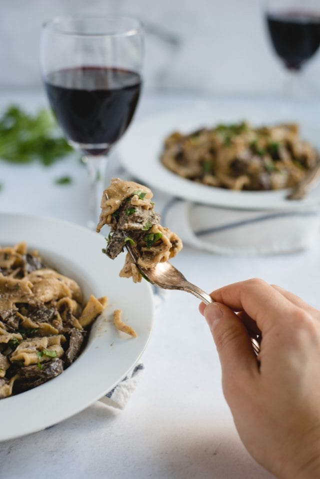 hand holding up bite of beef stroganoff with bowls and wine in background