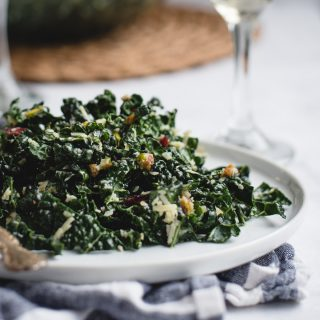 close up picture of kale salad on a white plate