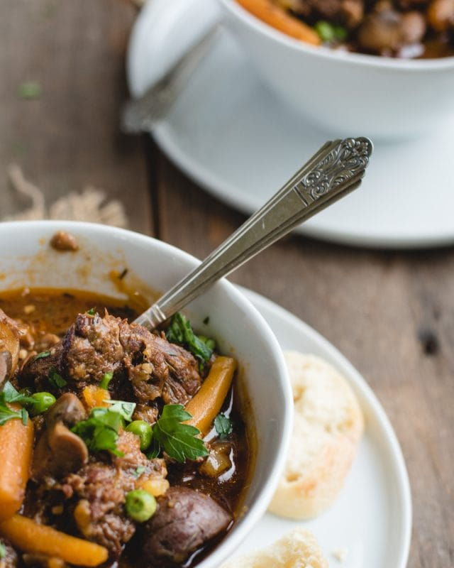 close up picture of irish beef stew with spoon sticking out of it