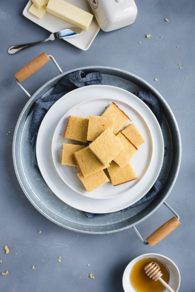 overhead picture of a plate of cornbread on a metal tray and blue background