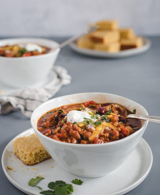 bowl of turkey chili with a second bowl and plate of cornbread in background