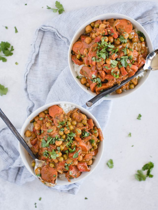 Overhead picture of two bowls full of chickpea curry on a white background