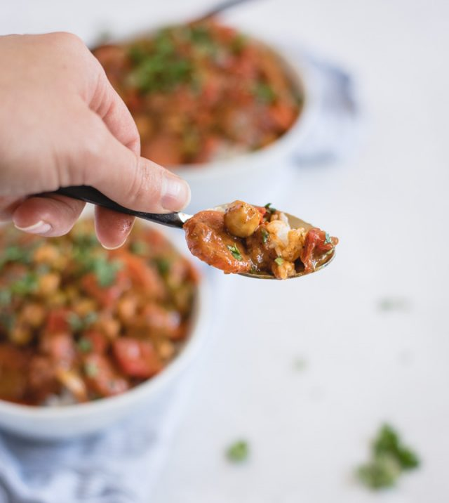Hand holding spoonful of vegan chickpea curry with bowls of curry in background