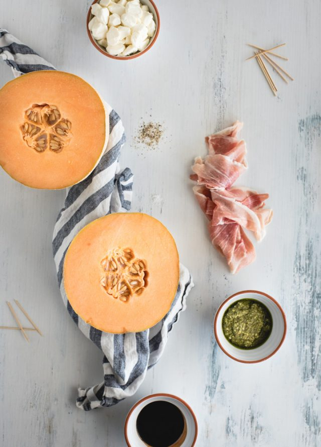 Overhead picture of all ingredients in prosciutto melon skewers laid out on a white background