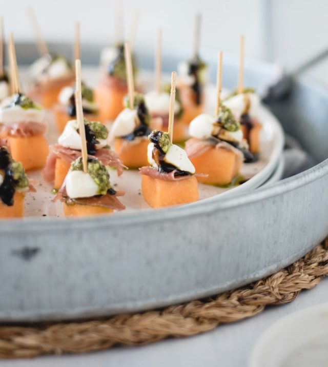 close up picture of metal tray with prosciutto melon skewers from a side view