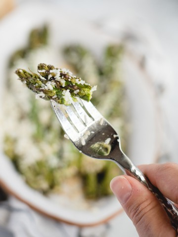 hand holding a fork with asparagus tips on it