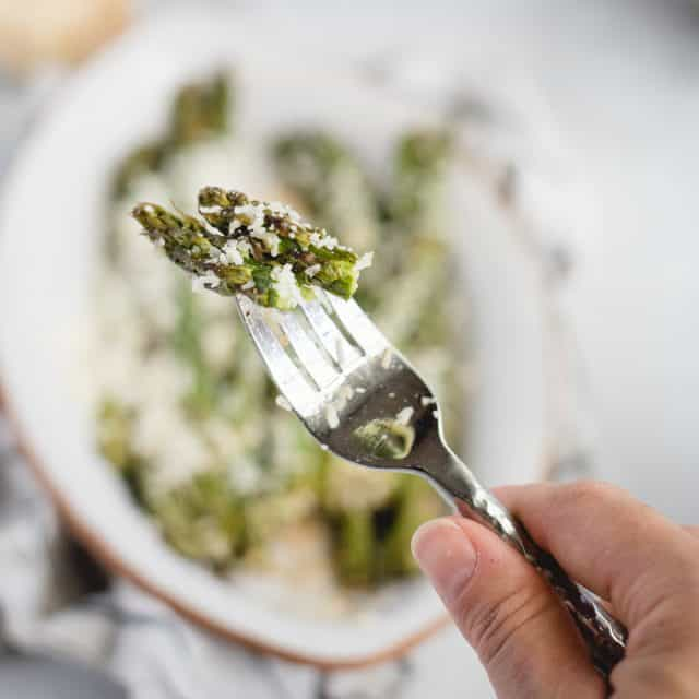 Hand holding a fork with asparagus on it against a light background