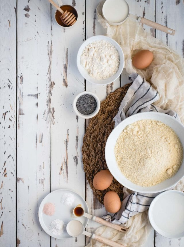 overhead picture of artful layout of ingredients for making almond poppy seed muffins on a weathered white table background