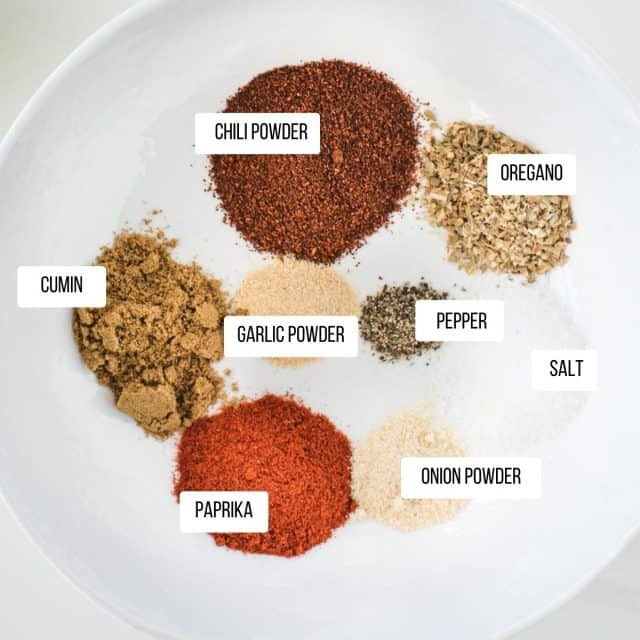 picture of chicken taco seasoning ingredients all labeled separately in a white bowl