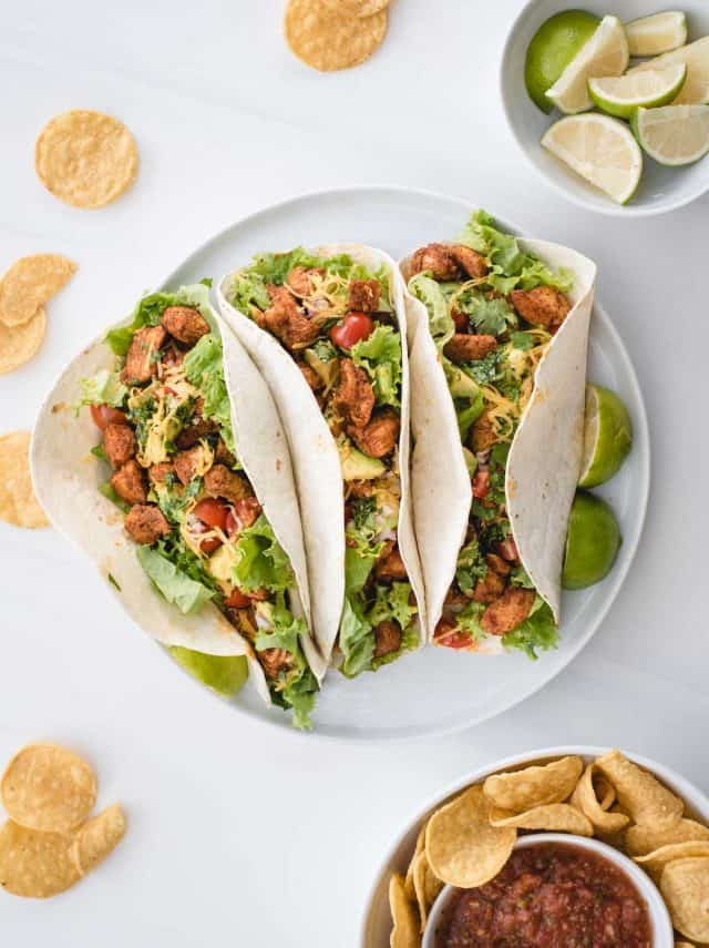 overhead table picture of chicken tacos on a white plate with a white background and chips sprinkled around and a bowl of limes