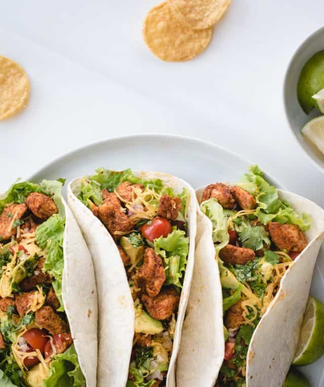 overhead picture of 3 chicken tacos on a white plate next to a bowl of limes and some chips