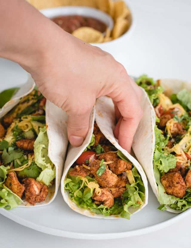 hand reaching down to a plate of tacos and grabbing a chicken taco