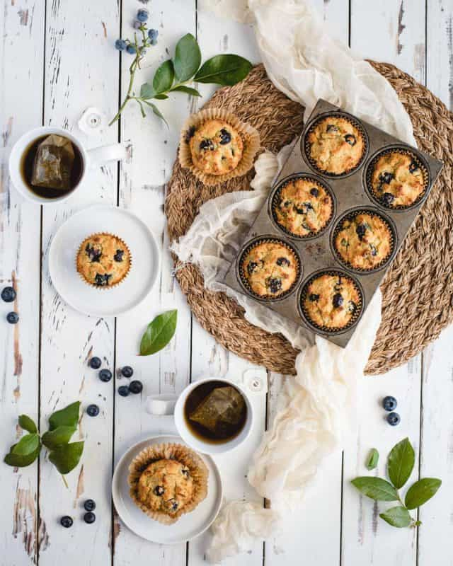 overhead picture of table scape with plates with blueberry muffins and cups of tea next to a tin of muffins