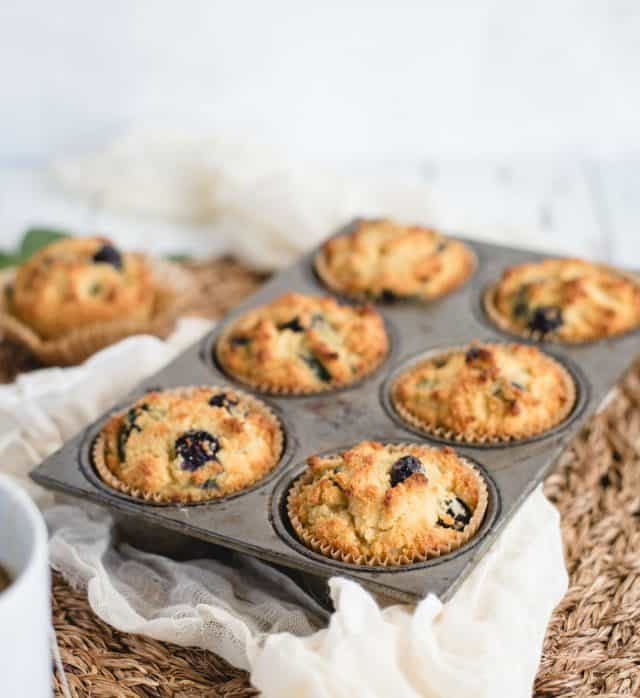 close up picture of a muffin tin full of six almond flour blueberry muffins