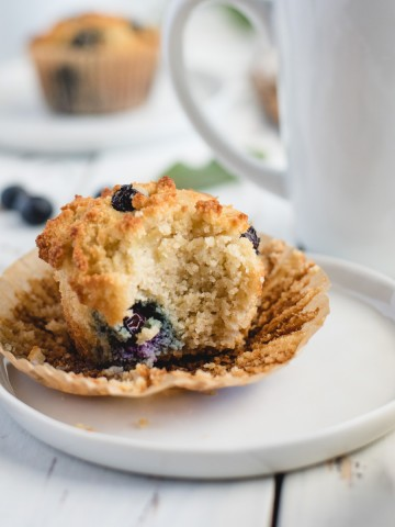 up close picture of gluten free blueberry muffin on a white plate